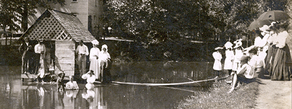 Picture of people being baptized in a lake.